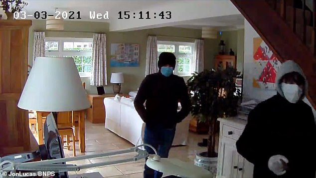 Security cameras inside the detached home show the family's golden retriever dog, Ted, barking loudly as the burglars enter the living room