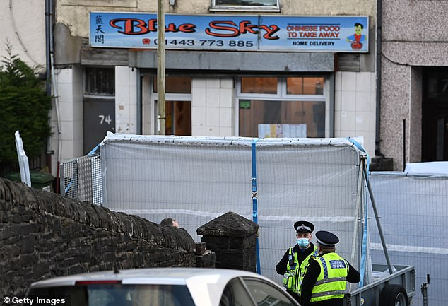 Two police officers seen standing in front of a cordon placed around the scene