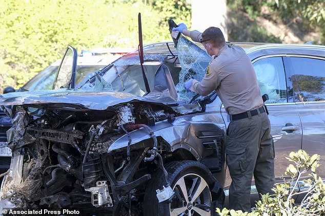 A law enforcement officer looks over a damaged vehicle following a rollover accident involving golfer Tiger Woods in the Rancho Palos Verdes suburb of Los Angeles