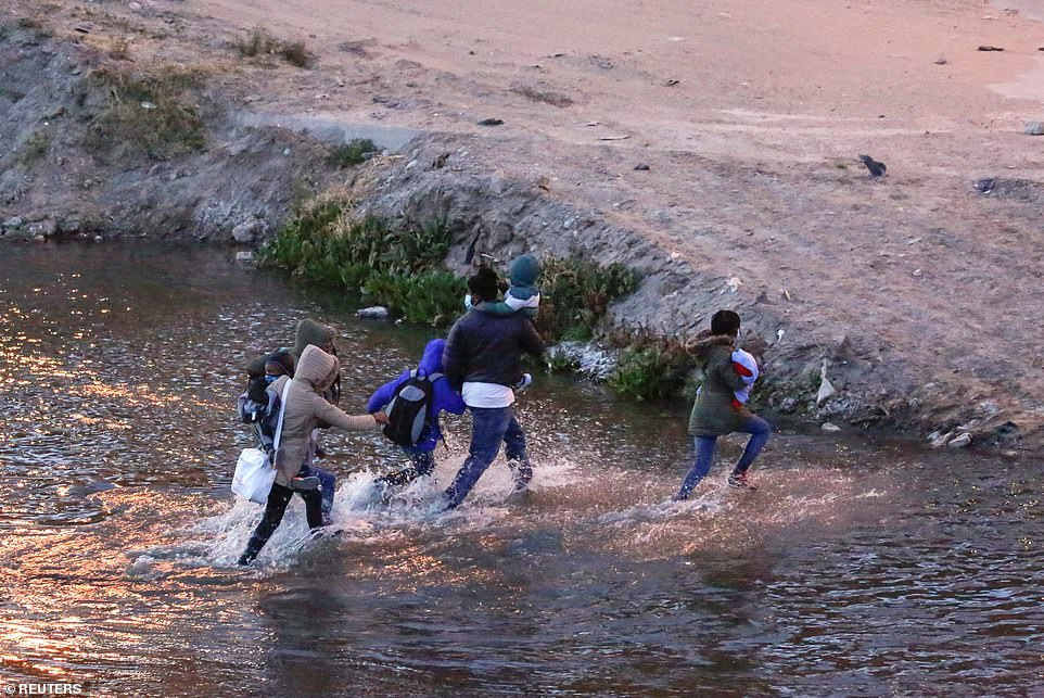 Donald Trump in a statement on Friday slammed President Joe Biden and his 'disastrous leadership' for allowing a 'spiraling tsunami' of migrants and 'criminals' over the United States border. Pictured, migrants cross the Rio Bravo river to turn themselves in to U.S Border Patrol agents to request for asylum in El Paso, Texas, on Thursday