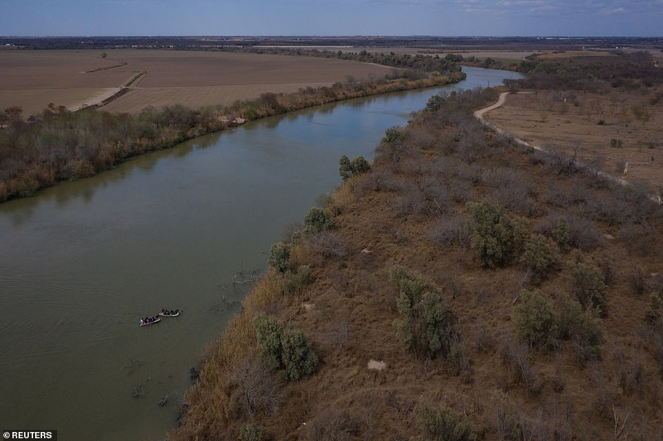 Smugglers use rafts to transport migrant families and children across the Rio Grande River into Texas from Mexico on Thursday. It comes as thousands of migrants cross the border in an influx that Trump has blamed on Biden's administration