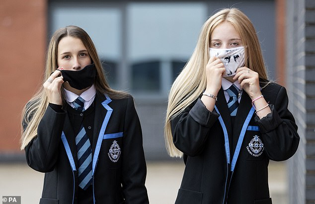 School children across England will be returning to class this week but will be expected to wair face masks if social distancing is impractical, pictured Leah McCallum, left, and Rebecca Ross, right, from St Columba's High School in Gourock, Scotland, in August 2020
