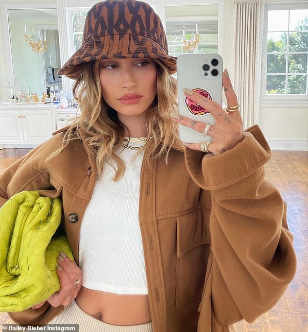 Designer darling: In a series of selfies, the 24-year-old model rocked an Ivy Park bucket hat, which she styled with a comfy oversized cardigan and cropped white tee