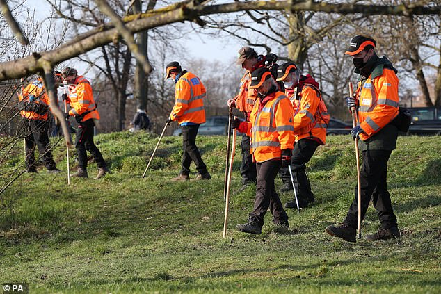Volunteers in high-visibility jackets from London Search and Rescue search the ground near Eagle Pond on Clapham Common yesterday as the search for missing Sarah Everard continues