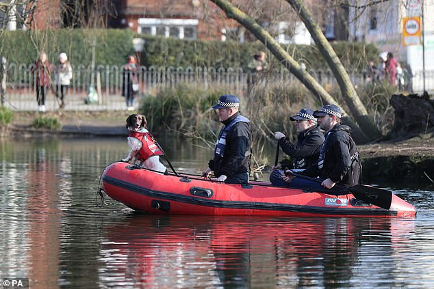 Pictured: Police officers with a sniffer dog search Eagle Pond on Clapham Common yesterday