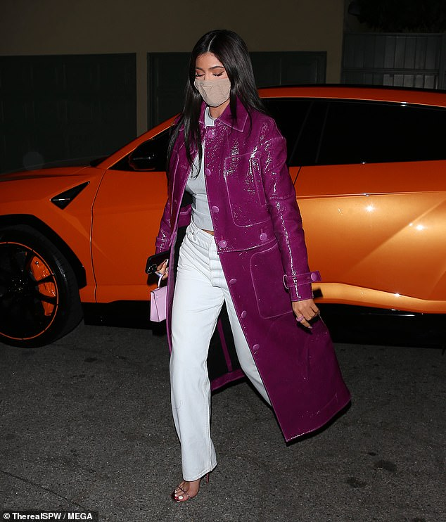 In Details: Kylie jumped out of her bright orange Lamborghini Urus and strutted around in a pair of shiny metallic magenta heels with jeweled details around the straps