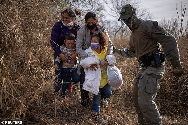 Migrants weep as they are escorted by a Texas State Trooper on Tuesday by the Rio Grande