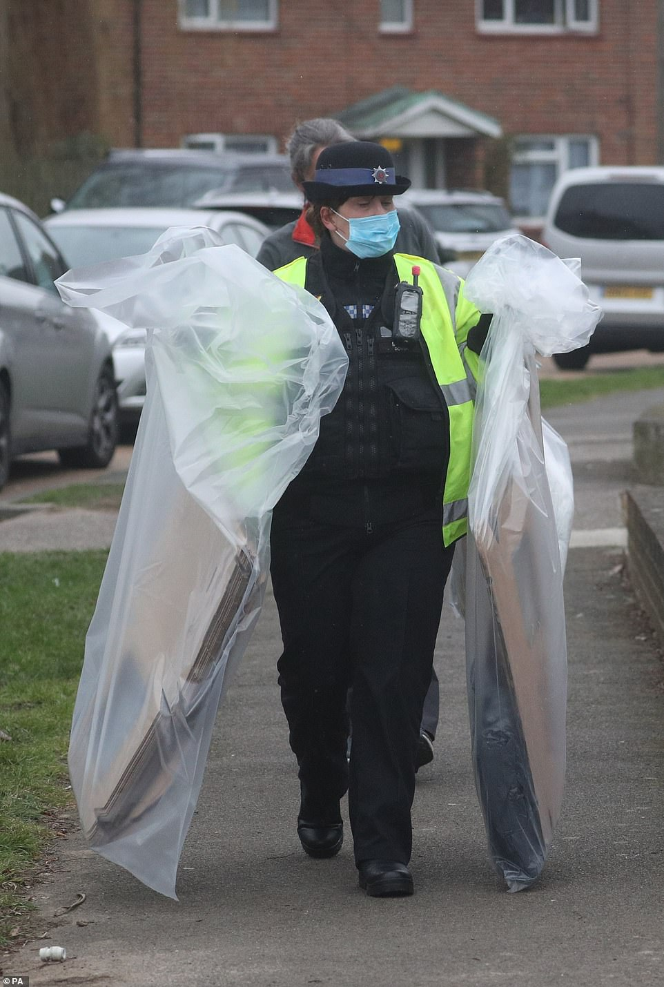 Police were seen taking away evidence in bags, including what appeared to be a laptop in the right plastic sack