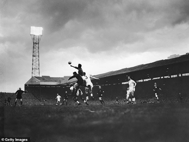 Manchester United keeper Harry Gregg, who was a survivor of the Munich air disaster, is pictured punching the ball clear during their 2-1 win over Milan months after the plane crash