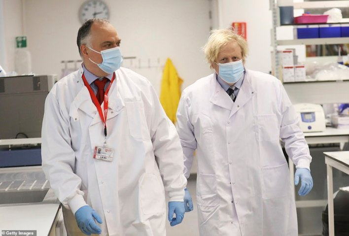 In yet another boost to the UK's rapidly advancing vaccine roll-out, the Government is set to take stock of 'bumper supply' of vaccines in the coming days. Pictured: Boris Johnson meets with Professor Jose Bengoechea during a visit at the Wellcome-Wolfson Institute For Experimental Medicine in Belfast