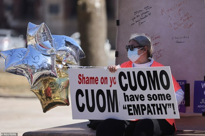 A protestor sits outside the New York State Capitol, following allegations that New York Governor Andrew Cuomo had sexually harassed young women on Friday