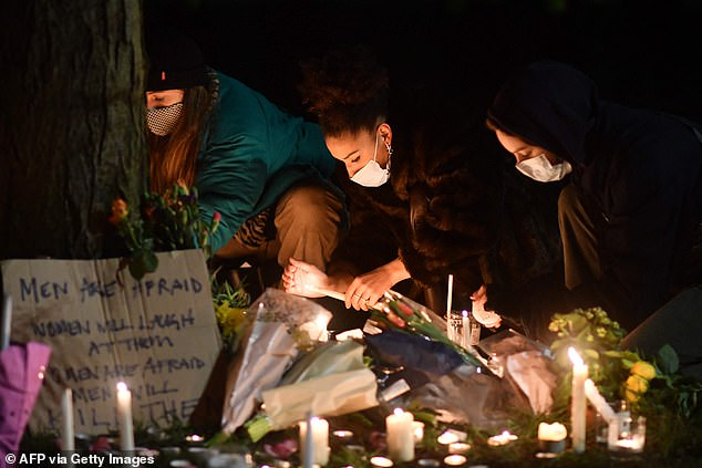 Well-wishers light candles around a tree in honour of Sarah Everard on Clapham Common, south London on March 13
