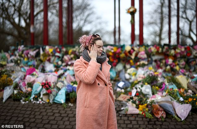 A woman reacts as she mourns at a memorial site at the Clapham Common Bandstand, following the kidnap and murder of Sarah Everard, in London, Britain March 14