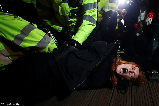 Police are seen arresting a women during clashes with demonstrators at aSarah Everard vigil in London