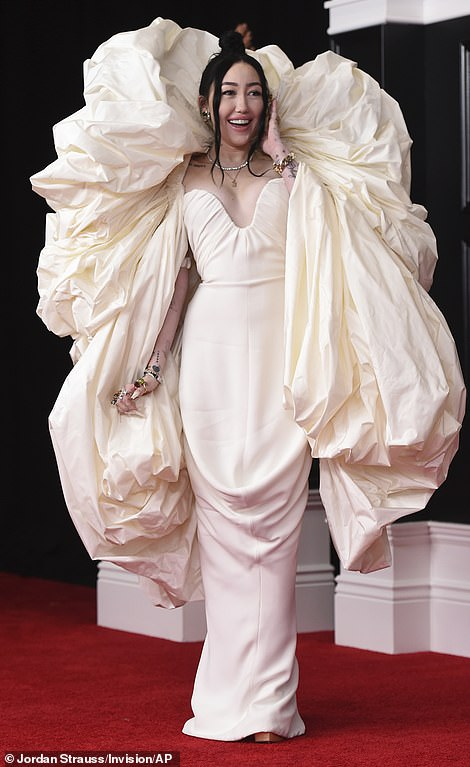 Standing out: Crooner Noah Cyrus arrived in a cream creation featuring a form fitting gown and voluminous cape-style attachment