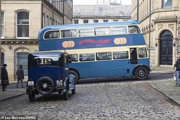 Throwback: While a vintage car chugged over a cobbles, a classic Routemaster bus also took to the road, plastered with an advert forMcVities and Price biscuits