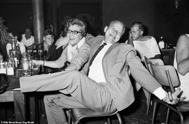 An elderly man and woman having a wild time pose for a photograph inside The Catacombs bar, Cape Town, South Africa, Monday February 5, 1968