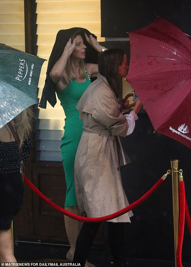 Whatever works! A wedding guests covered up with a coat over her head as a makeshift shield