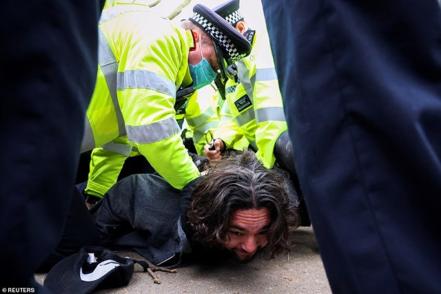 A demonstrator is pushed to the ground by policeu00A0after outrage at Metropolitan Police's handling of the Sarah Everard vigil last week