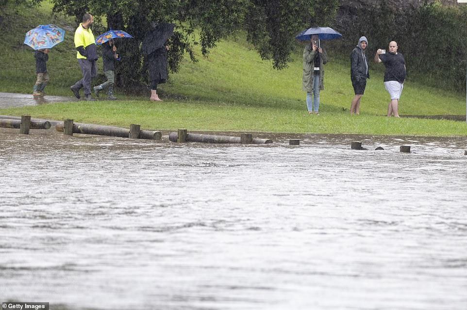 Windsor residents in Sydney's north-west braved the wet conditions to keep a close eye on the flooded Hawkesbury River