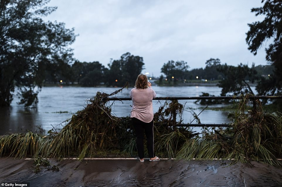 A woman takes a photo on Monday morning after the Nepean River in Sydney's western suburbs burst its banks