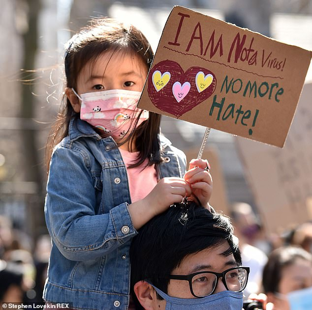 A man holds a child on his shoulders at the Rally Against Hate to protest the recent violence aimed at the Asian American community in New York on Sunday