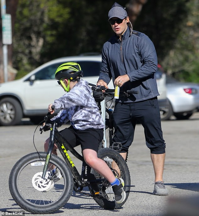 Bike ride: The Guardians of the Galaxy star, 41, took his eight-year-old child for a bike ride while hisu00A0 author wife, 31, carried their seven-month-old daughter around in a cloth baby carrier