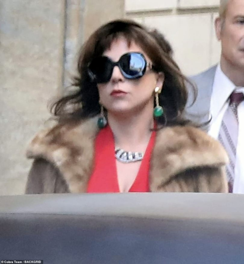 Looking good: Gaga caught the eye in a distinctive red dress and faux fur coat while stepping into Reggiani's designer shoes on location in Rome