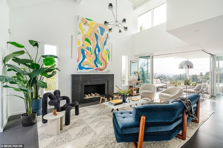 The lower levels offer a great room with white walls and a fireplace and an adjoining balcony/patio