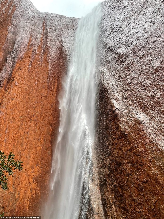 The iconic tourist attraction (pictured) has also transformed into a range of colors as the flowing water falls on Uluru