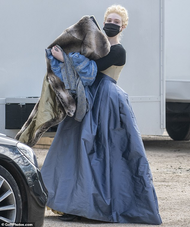On set:Elle Fanning covered her character's blossoming baby bump with a flowing blue satin skirt as she appeared on set for the first time on Wednesday