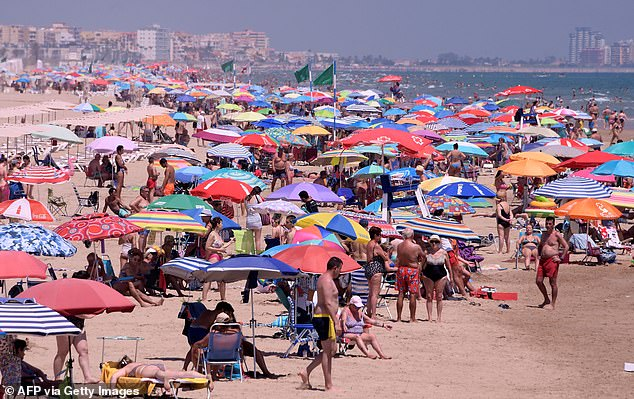 Holidaymakers are pictured enjoying a day at the Nord Beach in Gandia, near Valencia, on July 1 last summer
