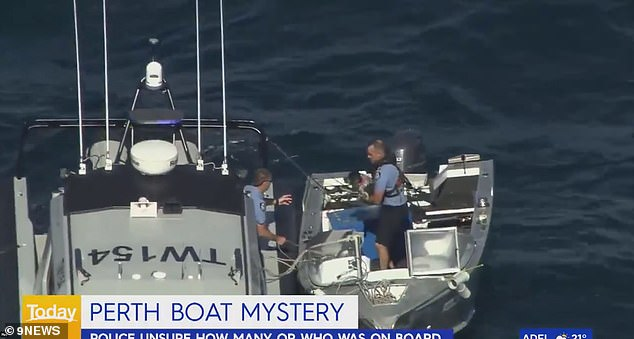 Vision shared by Nine News showed an officer carry a dog found on the dinghy, before passing it to a colleague on the police vessel