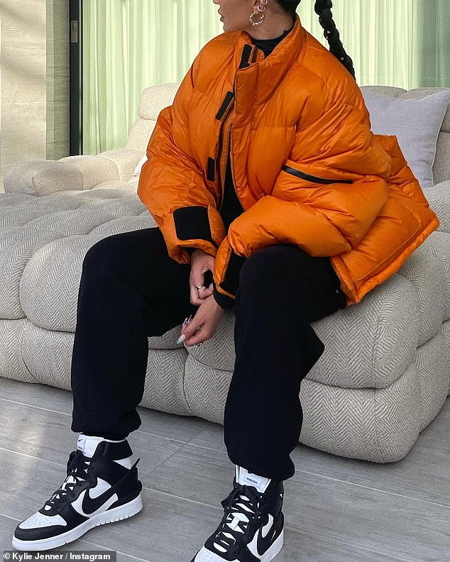 Versatile:One day Jenner looked business-ready in a pale blue shirt and trousers combo with slingback heels, before showcasing her sporty side in an orange puffer jacket and a pair of black and white Nike kicks