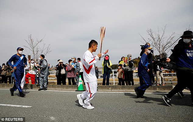 A torchbearer waves to spectators along the route of the Tokyo 2020 Olympic torch relay