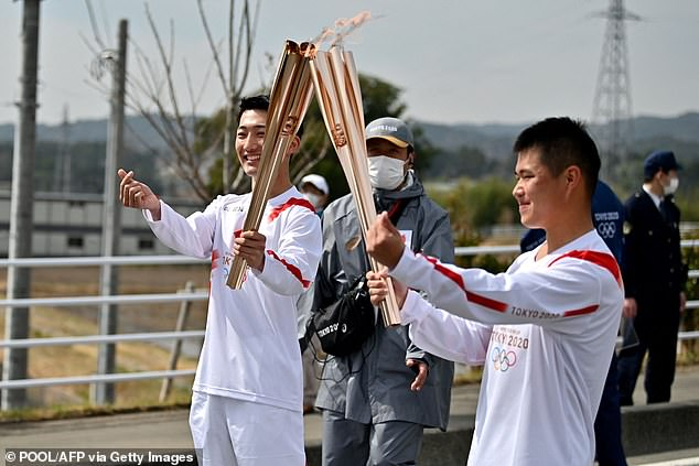 Japanese torchbearers pose during the first day of Tokyo 2020 Olympic torch relay at a torch kiss point in Naraha town, Fukushima