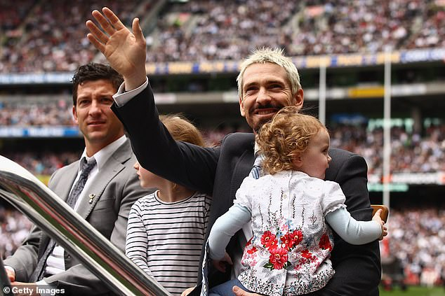 Akermanis makes his farewell to the AFL in the traditional pre-grand final lap of honour in 2010. He is pictured with daughters Charlotte and Sienna and former Port Adelaide and Fremantle star Josh Carr