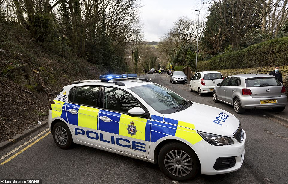 Police block the road leading to the school after parents gathered outside Batley Grammar School this morning