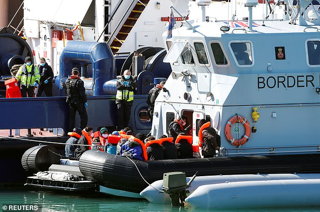 About 35 people were brought to Dover Marina on the stern of the Cutter Alert shortly after 11 a.m., which also towed the large gray rigid-hull inflatable boat in which they had attempted to make the dangerous journey.