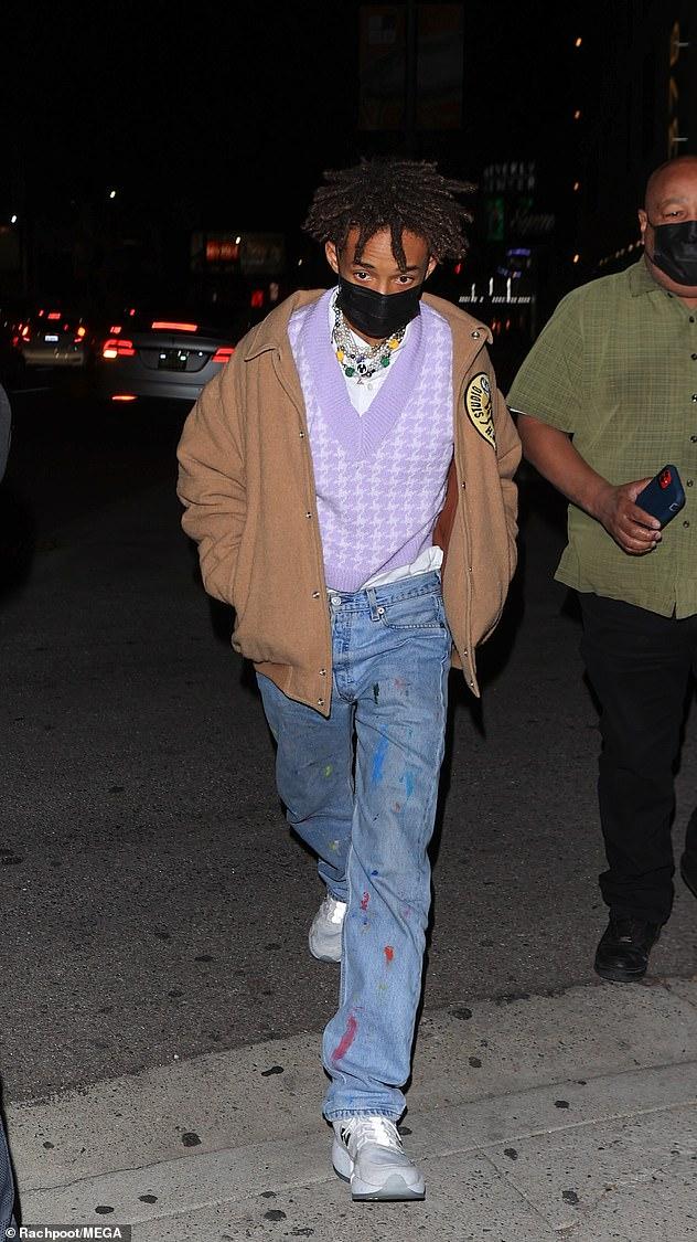 Le look de Jaden: Jaden portait également un pull lavande et un t-shirt blanc sous un manteau marron, ainsi qu'un jean bleu tacheté de peinture et des baskets New Balance grises