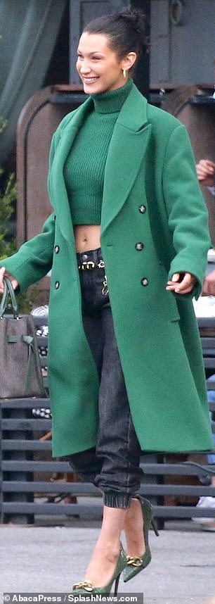 Emerald city: The brunette beauty paired her stylish look with dark grey jeans and matching emerald, crocodile-embossed leather heels