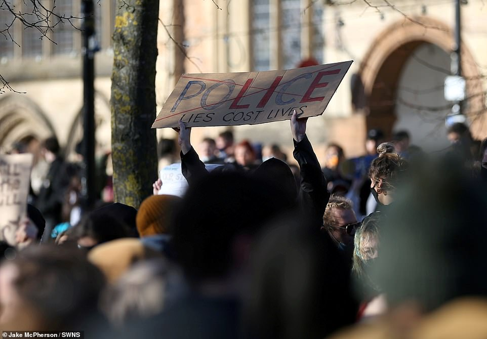 A hooded protest holds a sign that says 'Police lies cost lies' as hundreds gathered on College Green in Bristol city centre this afternoon