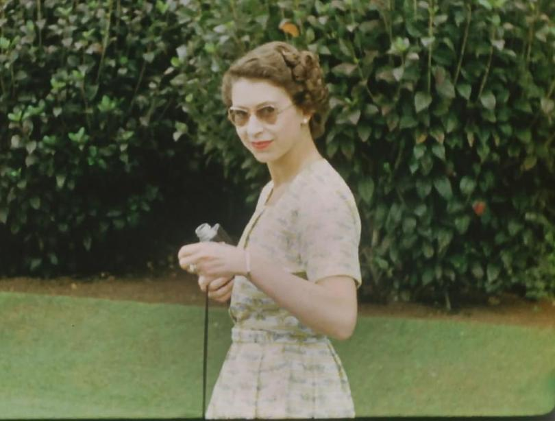 : A young Queen wearing sunglasses and holding a Cine camera on Christmas Day, 1953 in the middle of a gruelling 6 month tour,