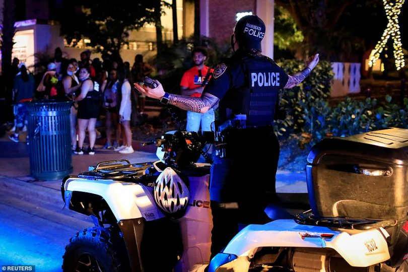 More police sit out on the street as they tell party goers to head home and enforce the curfew on Miami Beach