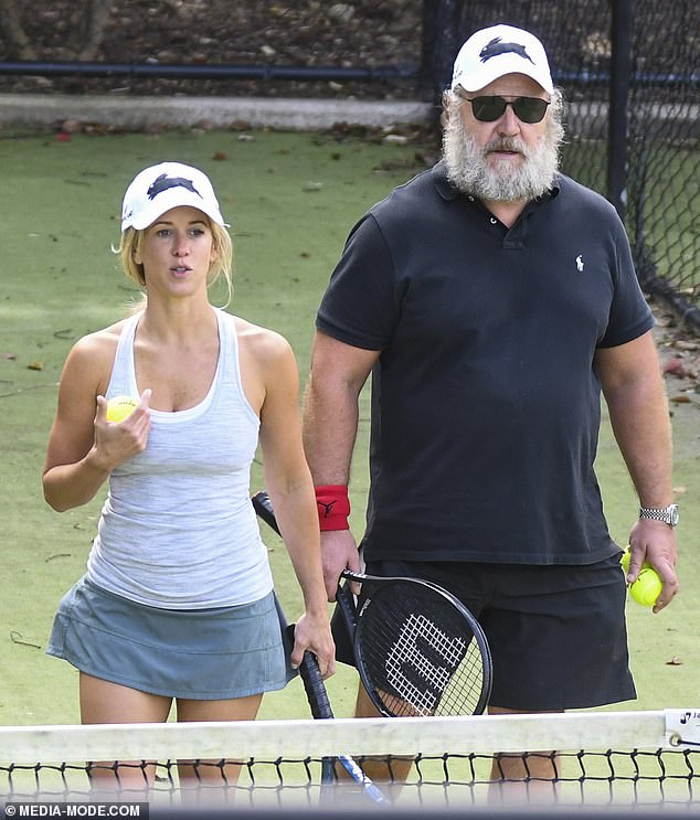 Hitting the court: On Friday, Russell Crowe, 56, showed off his scruffy beard as he worked up a sweat on a Sydney tennis court with girlfriend Britney Theriot, 30
