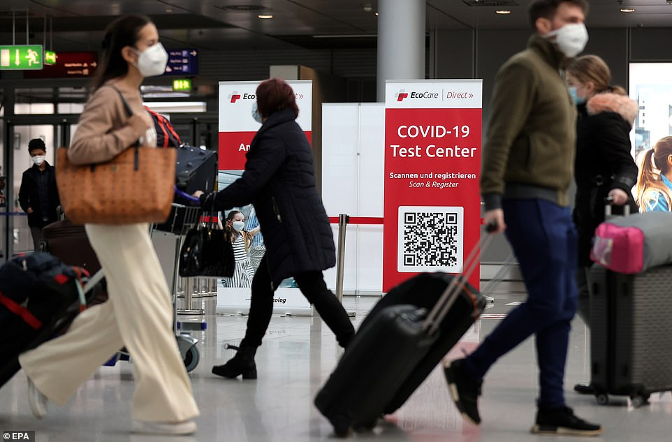 Pictured:Passengers walk past a sign for the coronavirus test center at the Dusseldorf International Airport in Dusseldorf, Germany, 26 March 2021. A sign directs travellers to a Covid-19 test center