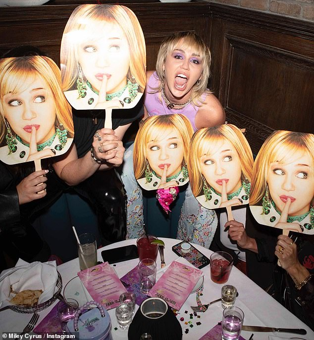 Then and now: Cyrus also posed with several of her friends, all of whom held up cardboard cutouts of her face
