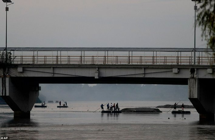 Migrants cross the Suchiate River fromGuatemala and Mexico, as Mexican immigration agents enforce limits on all but essential travel