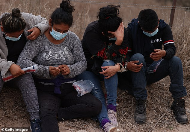 A group of people waits to be transported after being caught by U.S. Border Patrol agents crossing the border from Mexico on Saturday