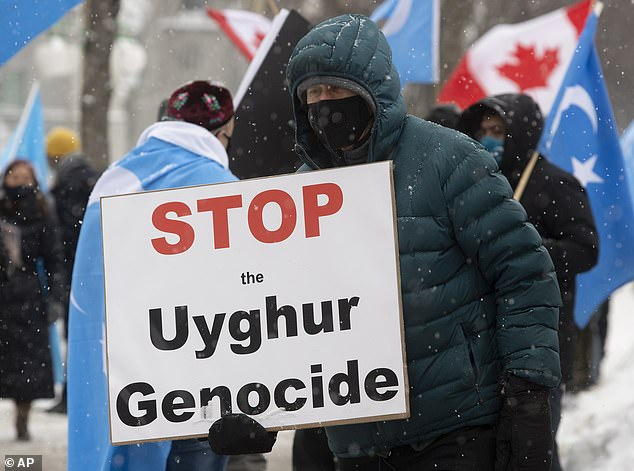 Western governments and rights groups have accused authorities in the western Chinese region of Xinjiang of detaining and torturing Uighurs in camps, drawing fierce denials from Beijing, who says the camps are vocational training centres that help combat religious extremism (pictured: Protesters gather outside the Parliament buildings in Ottawa, Ontario Monday, Feb. 22, 2021)